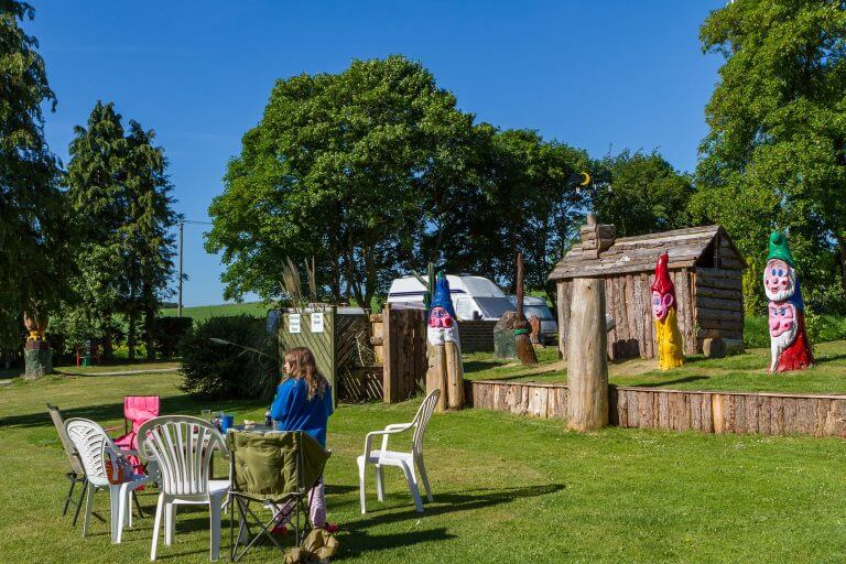 Tilshead grounds, with garden furniture and wooden cabin, Brades Acre Camping Site, Stonehenge, Wiltshire, Salisbury, camping, holiday lodges