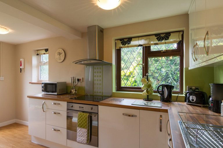 Modern kitchen with white cupboards, inbuilt cooker and hob, small kitchen appliances, window, Tilshead grounds, with garden furniture and wooden cabin, Brades Acre Camping Site, Stonehenge, Wiltshire, Salisbury, camping, holiday lodges