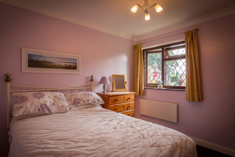 Double bedroom with double bed and light purple walls, oak chest of drawers, yellow curtains, Brades Acre Camping Site, Stonehenge, Wiltshire, Salisbury, camping, holiday lodges