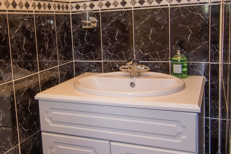 White oval basin, Modern bathroom with dark tiles, white basin and toilet, Brades Acre Camping Site, Stonehenge, Wiltshire, Salisbury, camping, holiday lodges
