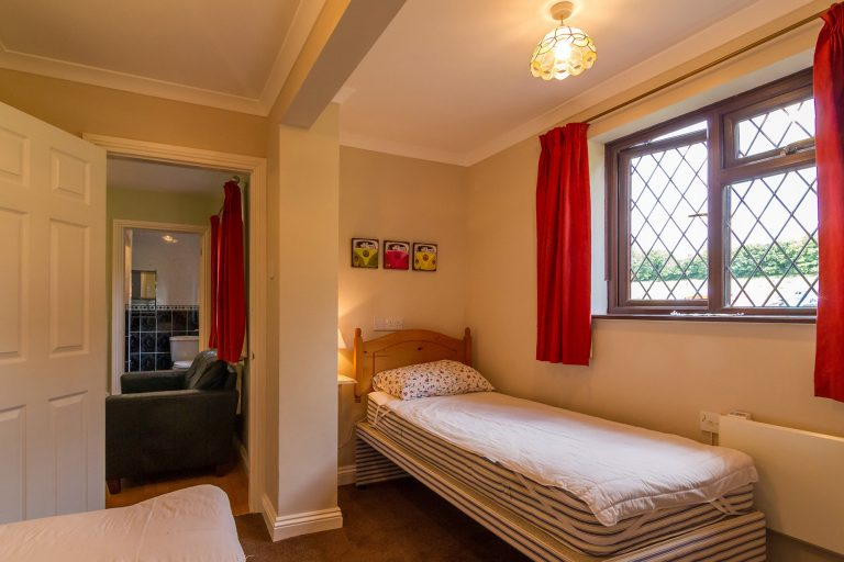 Twin room with two single beds, window with red curtains, Brades Acre Camping Site, Stonehenge, Wiltshire, Salisbury, camping, holiday lodges