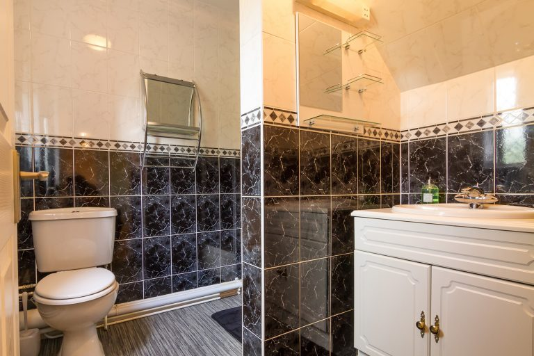 Modern bathroom with dark tiles, white basin and toilet, Brades Acre Camping Site, Stonehenge, Wiltshire, Salisbury, camping, holiday lodges