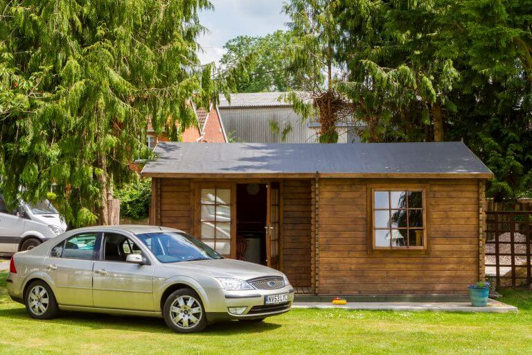 Log cabin with door open and silver car outside, Brades Acre Camping Site, Stonehenge, Wiltshire, Salisbury, camping, holiday lodges