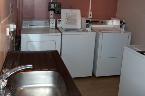 Laundry room with two washing machines, tumble dryer, and a sink