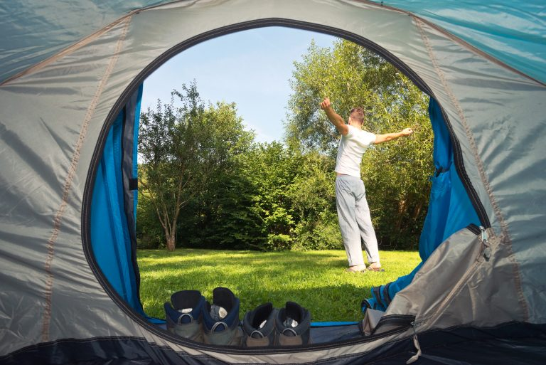 Man stretching outside of tent. View is looking out from inside the tent. Tilshead grounds, with garden furniture and wooden cabin, Brades Acre Camping Site, Stonehenge, Wiltshire, Salisbury, camping, holiday lodges